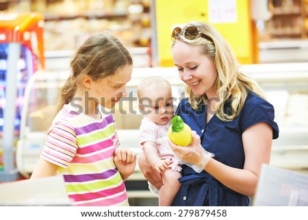 woman and little girls during family shopping at fruit vegetable supermarket - stock photo