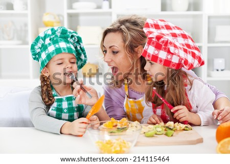 Woman and little girls preparing a fruit salad, tasting the ingredients - happy family moments - stock photo