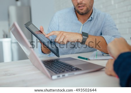 Woman and man are having a business meeting while working by using laptap and tablet pc