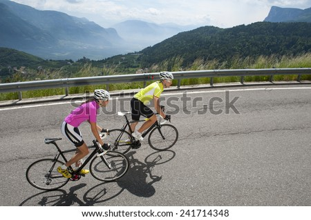 woman and man by uphill with road bike - stock photo