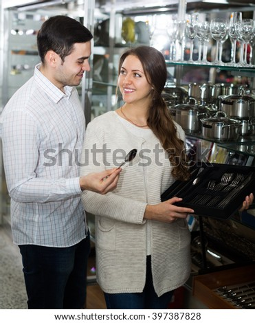 woman and man chooses flatware in the cookware section at shop