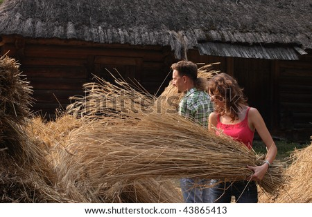 Woman and man cocking hay - stock photo