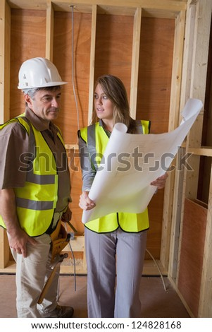 Woman and man discussing blueprints in construcion site - stock photo