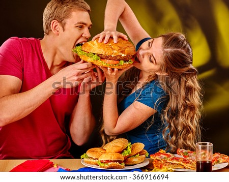 Woman and man feed each other fast food. Concept. - stock photo