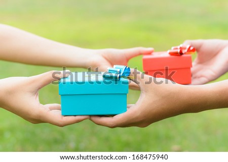 woman and man give a gifts, on green background - stock photo