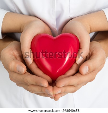 Woman and man holding red heart together in their hands. Love, assistance and healthcare concept - stock photo