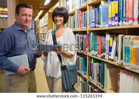 Woman and man holding tablet pc standing in library - stock photo