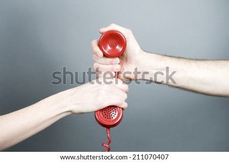 Woman and man holding telephone handset