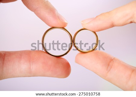 Woman and man holding wedding rings, close-up, on bright background - stock photo