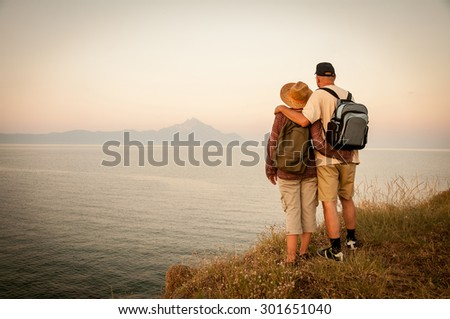 Woman and man hugging with backpacks standing on the top of the mountain in the sunset and enjoying the sea view and the mountain in the distance - stock photo