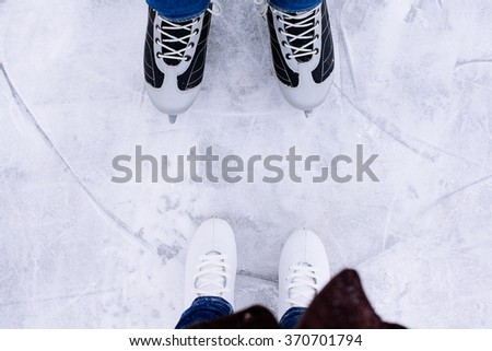 Woman and man  ice skating. winter outdoors on ice rink. ice and legs - stock photo
