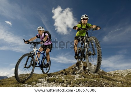 Woman and man in the mountain biking in the South Tirol Dolomite - stock photo
