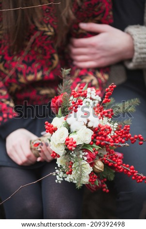 woman and man in the park in winter with a bouquet of red flowers - stock photo