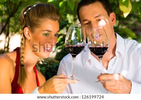 Woman and man in vineyard drinking red wine in the sunshine clinking the glasses - stock photo