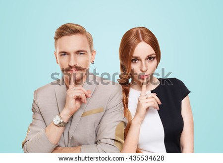 Woman and man keep secret. Couple shows hush sign, adultery, relationship issue, marriage cheating concept. Secret love, jealousy. Mystery, privacy, intimacy. Young beautiful couple isolated at blue. - stock photo