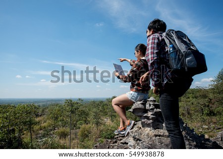 Woman and man looking map,Happy tourists sightseeing mountain with map