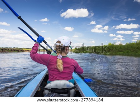 Woman and man man are kayaking on a river in beautiful nature