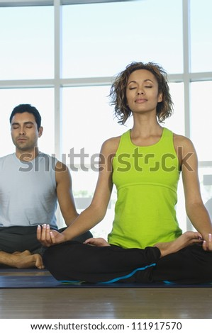 Woman and man meditating in lotus position - stock photo