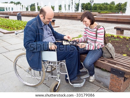 woman and man on an wheelchair play a chess - stock photo