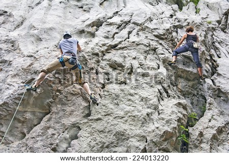 Woman and man rock climbing on a high rock wall