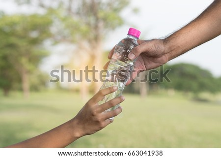 woman and man's hand holding drinking water bottle on blurred green bokeh background