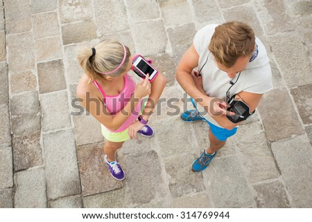 Woman and man setting their phones before workout - stock photo