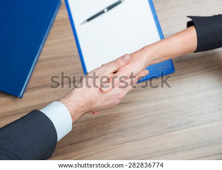 Woman and man shaking hands over paper and pen on the table. - stock photo