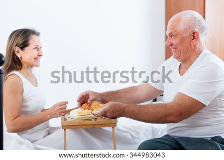 Woman and man sitting on  white bed near tray with breakfast .