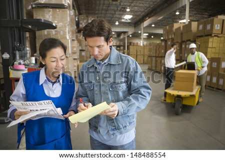 Woman and man talking in distribution warehouse with workers in background
