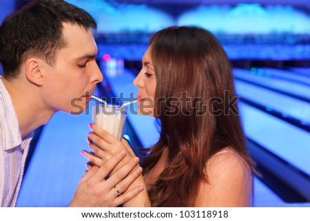 Woman and man together drink milk cocktail from one glass in bowling - stock photo