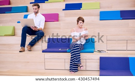 Woman and man using technology while sitting on steps