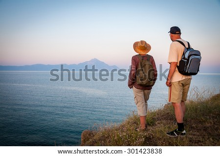 Woman and man with backpacks standing on the top of the mountain in the sunset and enjoying the sea view and the mountain in the distance - stock photo
