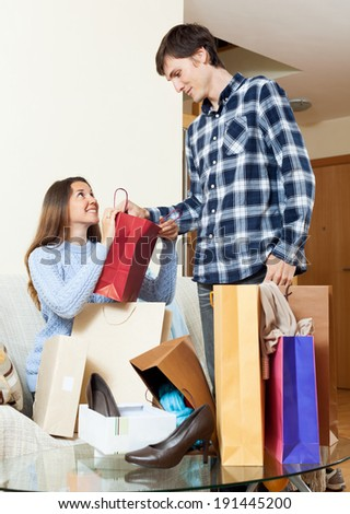 Woman and man with clothes and bags smiling in home