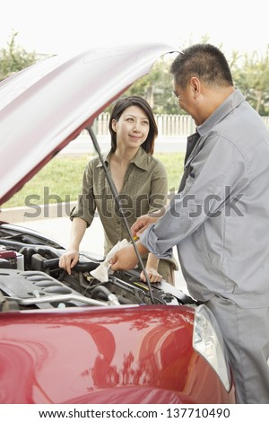 Woman and Mechanic Working on Car - stock photo