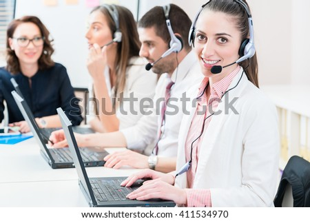 Woman and men working as call center agents giving helpdesk service - stock photo