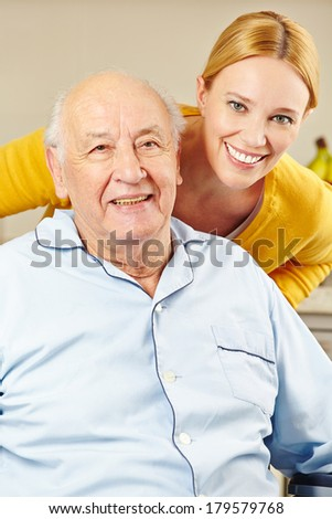 Woman and old man in wheelchair smiling together - stock photo