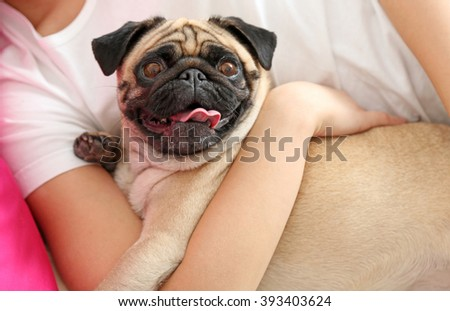 Woman and pug dog lying in bed - stock photo