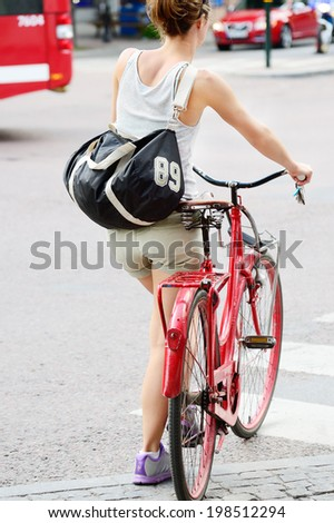 Woman and red bike. - stock photo