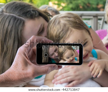 Woman and small baby girl laughing and cuddling in photo being taken by male hand on smartphone