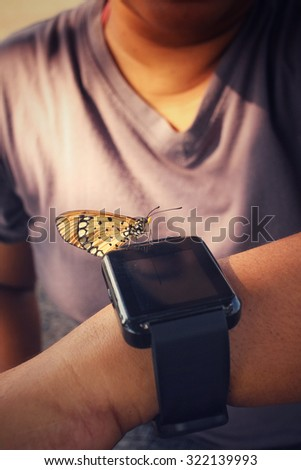 Woman and smartwatch with butterfly on hand