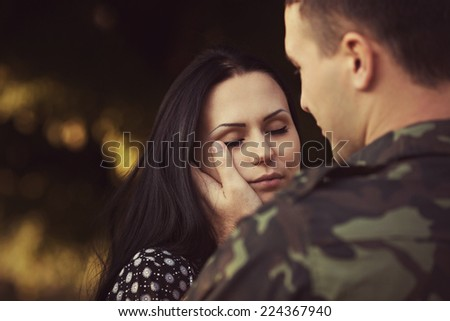 Woman and soldier in a military uniform say goodbye before a separation - stock photo