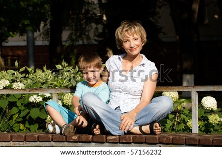 Woman and son sitting on the bench in park