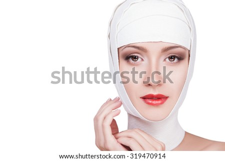 Woman and Surgery.Beautiful woman with bandages on her head, her face beautiful make-up and red lips. Lovely portrait of a female face in bandage with red lipstick on her lips, half-Fake. Beauty