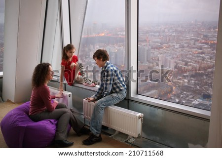 Woman and two children sitting next to a large window with a view of the evening city - stock photo