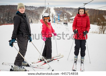 Woman and two children ski in winter at ski resort.