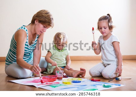 Woman and two children together painting with brushes on floor - stock photo