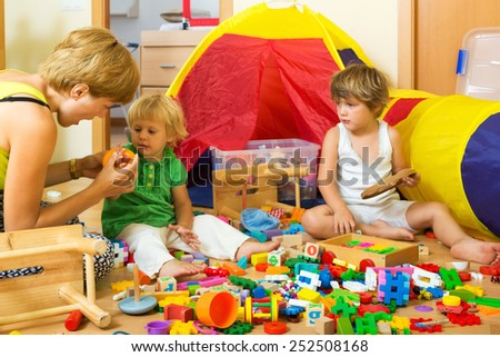 Woman and two children together playing with  toys indoor - stock photo