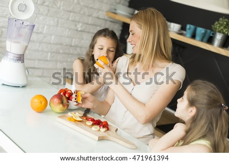 Woman and two little girls preparing fruits for smoothie