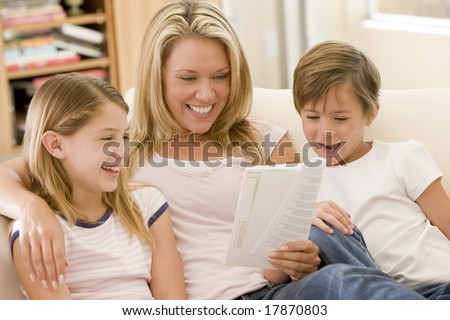 Woman and two young children in living room reading book and smiling - stock photo