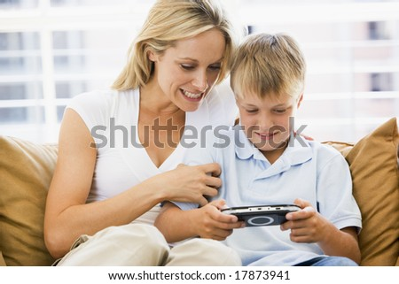 Woman and young boy in living room with handheld video game smiling - stock photo